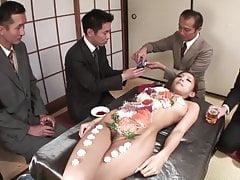 Gli uomini d'affari mangiano sushi dal corpo di una ragazza nuda