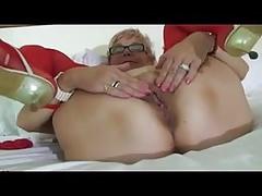 Sexy Oma in roten Dessous masturbiert im Bett