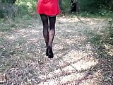 High heels in nylon stockings with an arrow and red dress