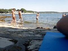 Ragazza calda sulla spiaggia nudista