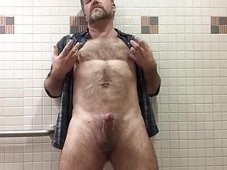 Strips and strokes his hard cock...
