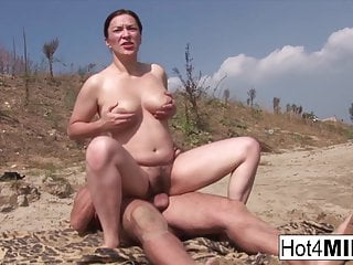 Busty milf with natural tits fucks beach...