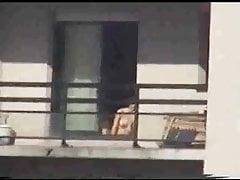 Neighbor sunbathing on balcony