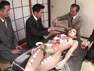 Business men eat sushi out of a amp...